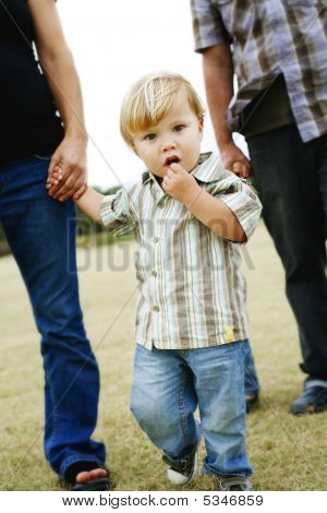Child Walking With Parents In A Park.