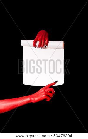 Red devil hands holding paper scroll and pointing at signature place, isolated on black background