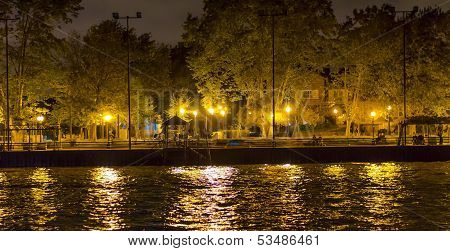 Sidewalk By Canal, Lit By Several Lamp Posts, And Small Pier