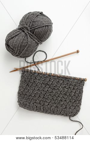 Incomplete knitting project with ball of grey wool