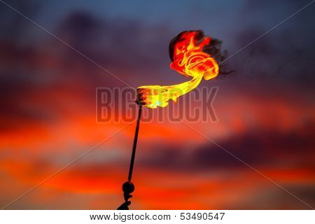Fire torch at sunset sky with red clouds background