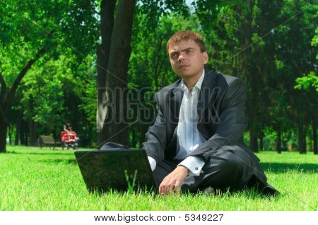 Businessman In A Park On The Grass Wiht Laptop