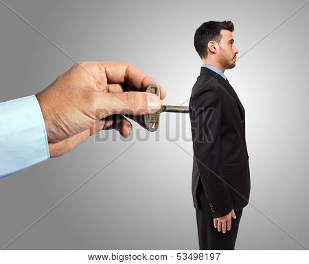 Hand winding up a mechanical businessman