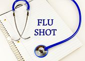 pic of flu shot  - Flu shot text over a white notebook wrapped in a blue stethoscope - JPG