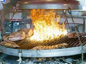 foto of brazier  - roasted meat on large brazier in country fair - JPG