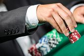foto of gambler  - Gambler stakes the pile of chips - JPG