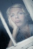 stock photo of rainy day  - Bored Woman Looking at the Rainy Weather By the Window Frame - JPG