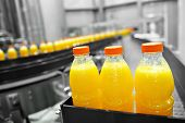 picture of sugar industry  - Orange juice bottles on factory assembly line