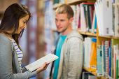foto of she-male  - Blurred young male looking at female as she reads a book against bookshelf in the library - JPG