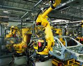 foto of welding  - yellow robots welding cars in a production line - JPG