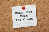 stock photo of differential  - The phrase Stand Out From The Crowd on a paper note pinned to a cork notice board - JPG