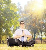 foto of stressless  - Young businessperson with eyeglasses doing yoga exercise seated on a green grass in a park - JPG