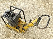 stock photo of vibration plate  - Old yellow plate compactor on aggregate bed - JPG