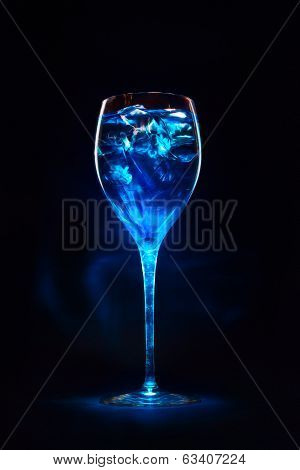 Amazing Blue Cocktail With Ice Cubes On Dark Background. Magic Light.