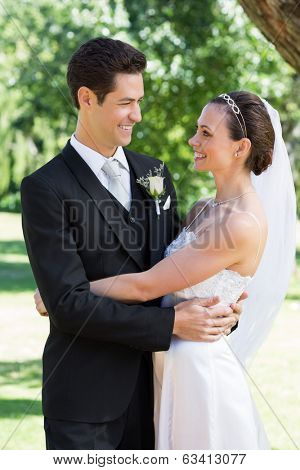 Affectionate newly wed couple embracing each other in garden