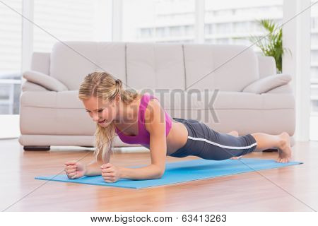Fit blonde in plank position on exercise mat at home in the living room