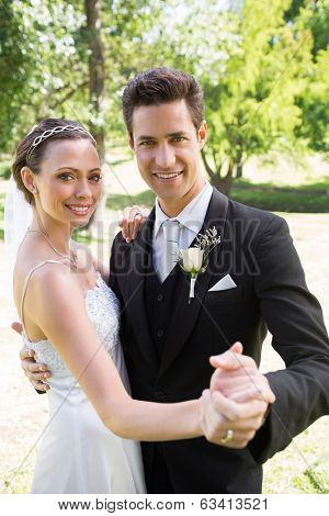 Portrait of happy newly wed couple dancing together in garden