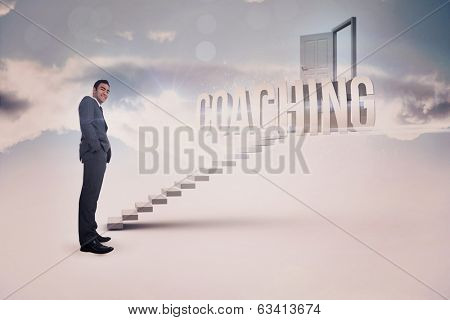 The word coaching and smiling businessman standing against white steps leading to open door