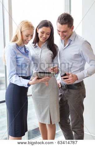 business and office concept - smiling business team working with tablet pcs and smartphones in office