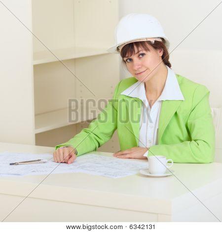 Chica en casco protector se sienta en mesa en oficina