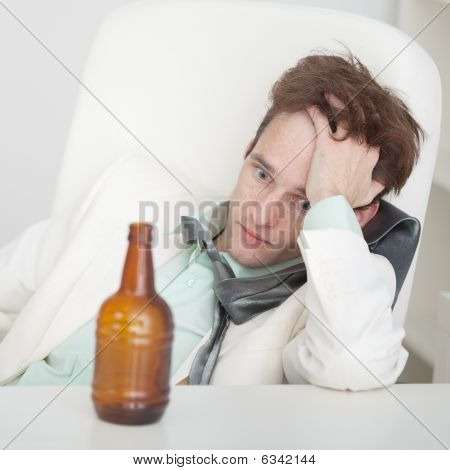 Person Suffers From Hangover Sitting At A Table
