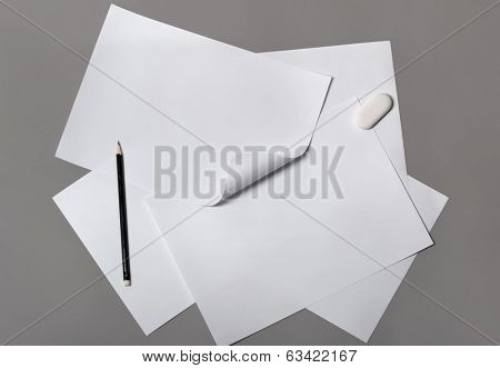 Stack of paper with pencil on gray background