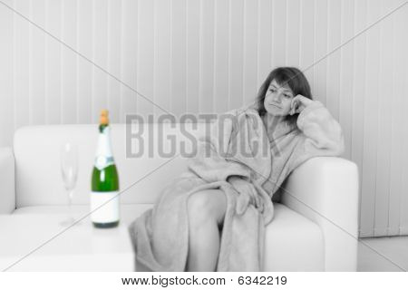 Lonely Young Woman Sits On Sofa And Looks At Wine Bottle