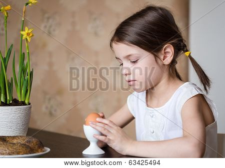 Preschooler girl with Easter egg for breakfast