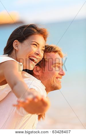 Couple on beach having fun laughing in love on romantic honeymoon travel vacation summer holidays romance. Young happy lovers, Asian woman and Caucasian man doing joyful piggybacking ride outdoors.