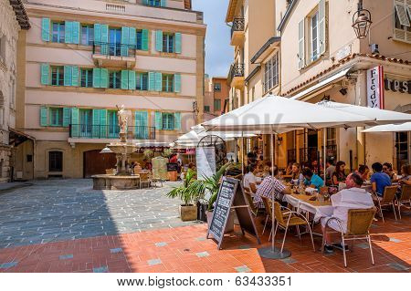 MONACO-VILLE, MONACO - JULY13, 2013: People having dinner in restaurant on small quiet square with fountain surrounded by houses in Monaco-Ville, Monaco  - popular touristic resort and place to visit.