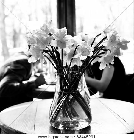 Table in the cafe with lent lily and loving couple at background. Date. Urban lifestyle. Black and white.