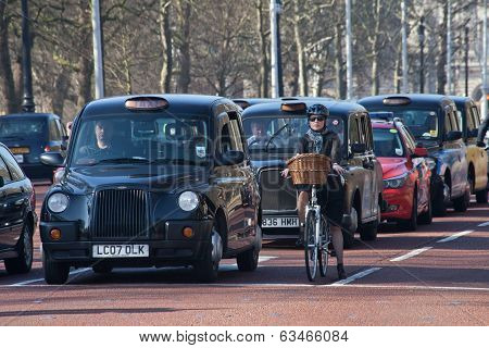 Row of black london cabs in a traffic stop with a female cyclist