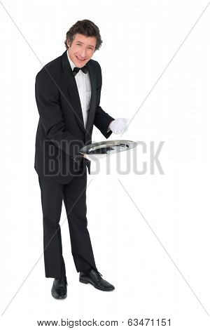 Portrait of confident waiter showing empty tray over white background