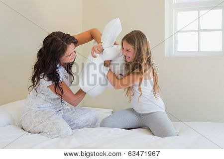 Happy mother and daughter pillow fighting in bed at home