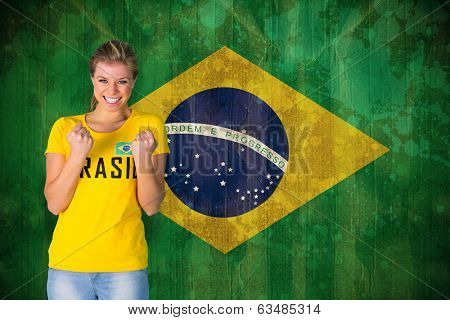 Excited football fan in brasil tshirt against brazil flag in grunge effect