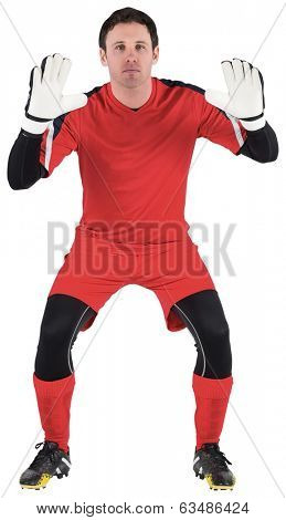 Goalkeeper in red ready to catch on white background