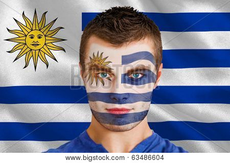 Composite image of serious young uruguay fan with facepaint against digitally generated uruguay national flag