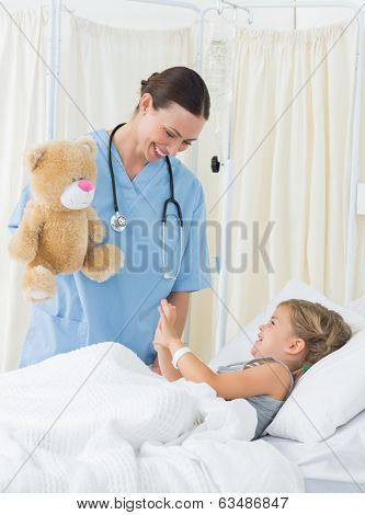 Playful female doctor entertaining sick girl with teddy bear in hospital bed