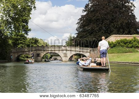 CAMBRIDGE, UK - AUGUST 18: Professional punter in busy River Cam with tree lined bank to one side and the oldest bridge in Cambridge, Claire bridge, in the far horizon. August 18, 2013 in Cambridge.