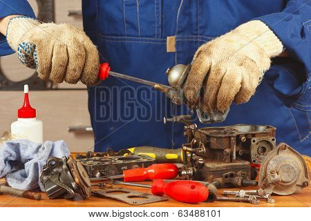 Repairman repairing parts of the engine in workshop