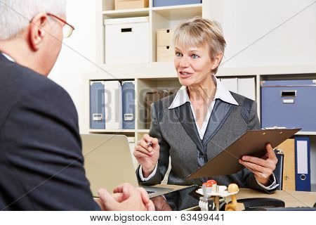 Elderly female consultant in bank talking to senior customer