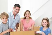 Portrait of happy family of four unpacking cardboard box in new house
