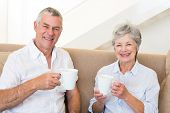 Senior couple sitting on couch drinking coffee smiling at camera at home in living room
