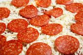 stock photo of frozen food  - Frozen pepperoni and Cheese pizza on a wooden cutting board - JPG