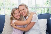 Portrait of happy mother and daughter embracing on sofa at home