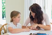 Young woman helping daughter in homework at table in house