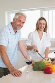 Cheerful couple making dinner together at home in the kitchen