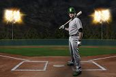 stock photo of ball cap  - Baseball Player on a Green Uniform on baseball Stadium.