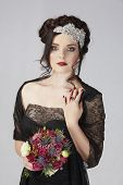 Beautiful brunette young model with braided hair with shiny crown wearing black lace dress in studio