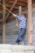 foto of tire swing  - Young boy swinging on a rope swing in the barn - JPG